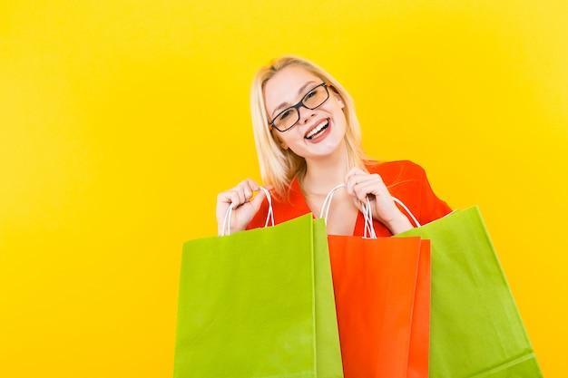Mujer rubia vestida con bolsos