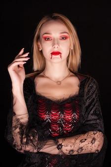 Mujer rubia vestida como un vampiro con sangre en los labios sobre fondo negro. disfraz de halloween.