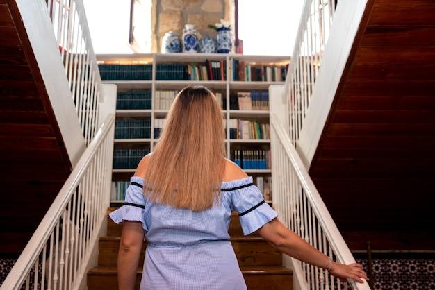 Mujer rubia en vestido azul subiendo las escaleras de madera de su casa.