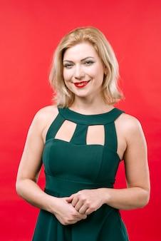 Mujer rubia en vestido verde sonriendo