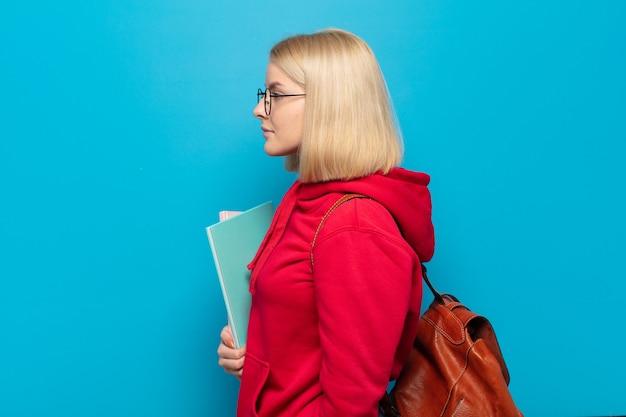 Mujer rubia en vista de perfil mirando para copiar el espacio por delante, pensando, imaginando o soñando despierto