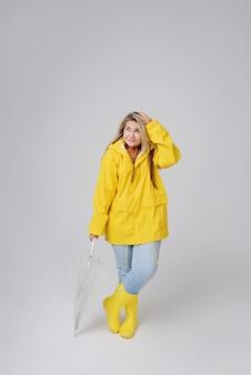 Mujer rubia vistiendo impermeable amarillo con paraguas transparente comprobando el clima si está lloviendo