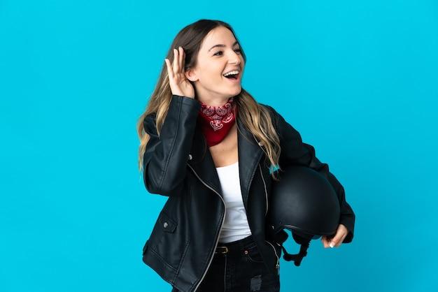 Mujer rumana sosteniendo un casco de motocicleta aislado en azul escuchando algo poniendo la mano en la oreja