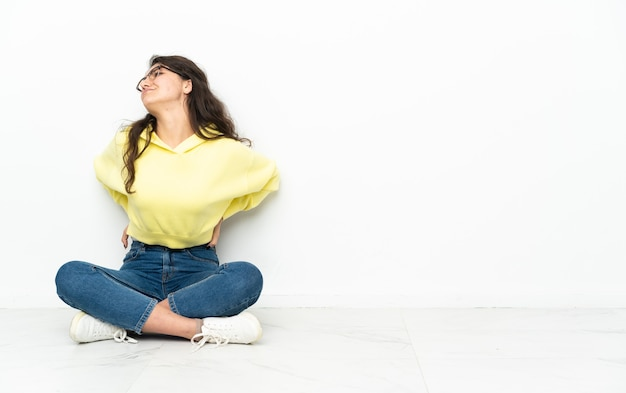 Mujer rusa adolescente sentada en el suelo sufre de dolor de espalda por haber hecho un esfuerzo