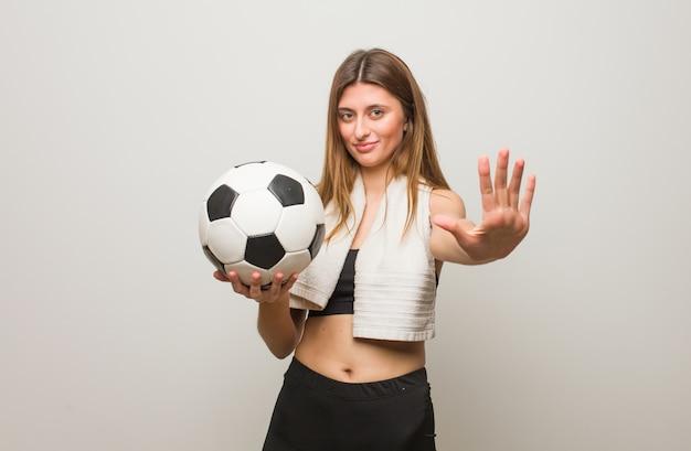 Mujer rusa de la aptitud joven que muestra el número cinco. sosteniendo un balón de fútbol.