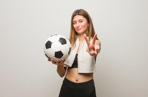 Mujer rusa de la aptitud joven que muestra el número dos. sosteniendo un balón de fútbol.