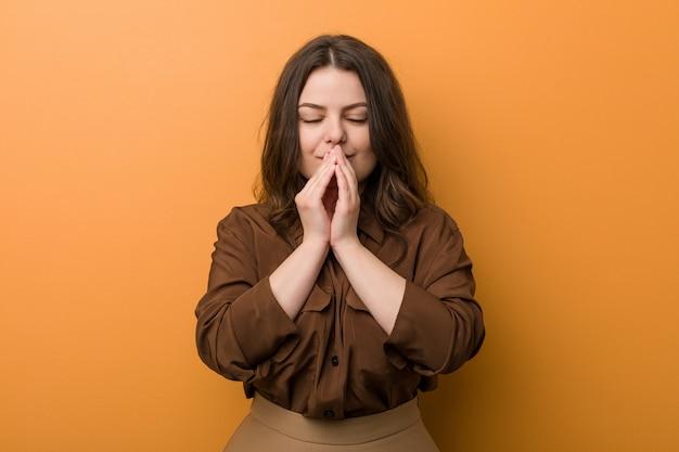 La mujer rusa con curvas joven que lleva a cabo las manos en ruega cerca de boca, se siente confiado.
