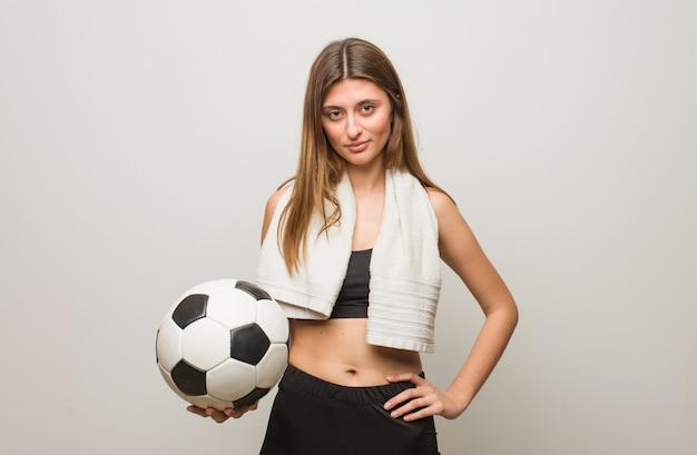 Mujer rusa fitness joven con las manos en las caderas. sosteniendo un balón de fútbol.