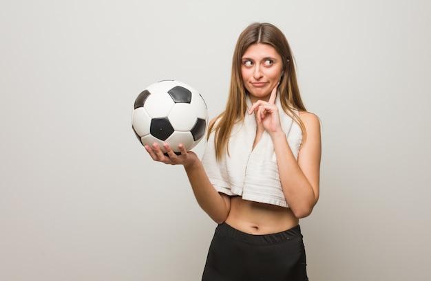 Mujer rusa fitness joven pensando en una idea. sosteniendo un balón de fútbol.