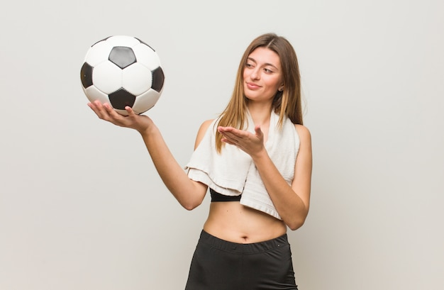 Mujer rusa fitness joven sosteniendo algo con la mano. sosteniendo un balón de fútbol.