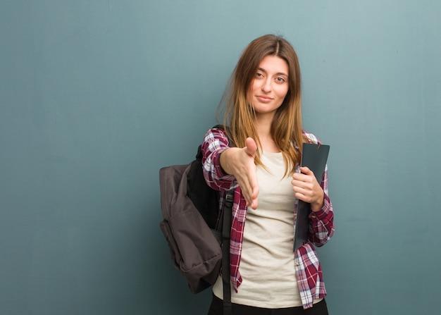 Mujer rusa joven estudiante extendiéndose para saludar a alguien