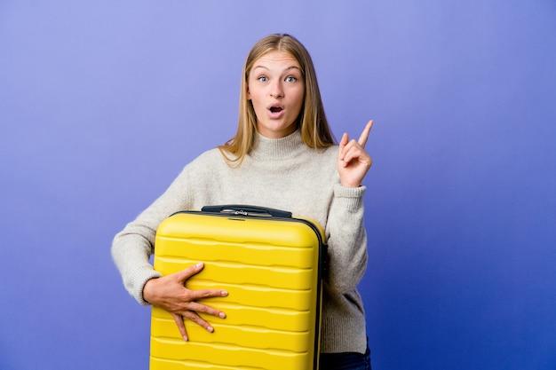 Mujer rusa joven que sostiene la maleta para viajar con una gran idea, concepto de creatividad.