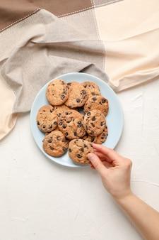 Mujer con sabrosas galletas de chispas de chocolate sobre fondo gris, vista superior.