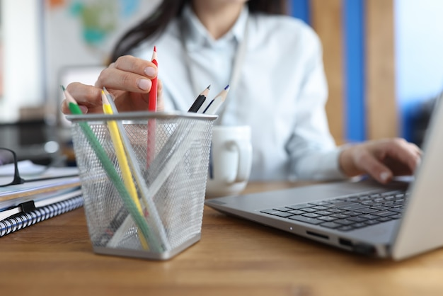 La mujer saca el lápiz del organizador en el lugar de trabajo