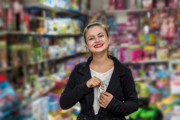 Mujer sacando dólares del bolsillo en la tienda de juguetes