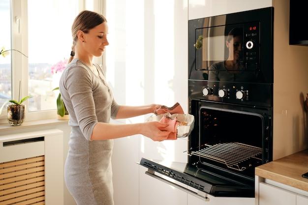 Mujer sacando pastel de jem recién horneado del horno