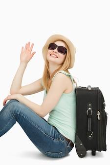 Mujer sainsing su mano mientras estaba sentado cerca de una maleta