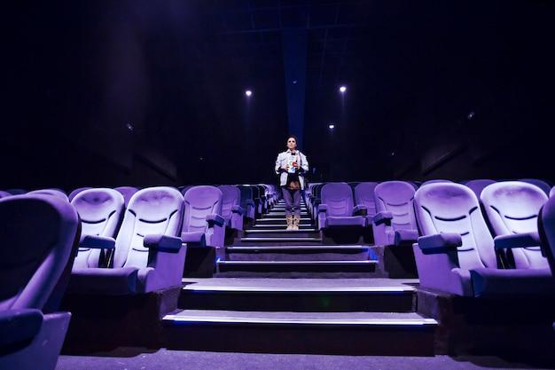 Mujer en la sala de cine iluminada
