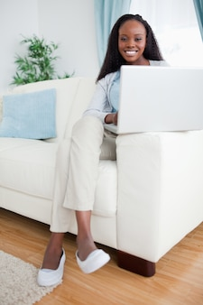 Mujer en la sala de estar usando su computadora portátil