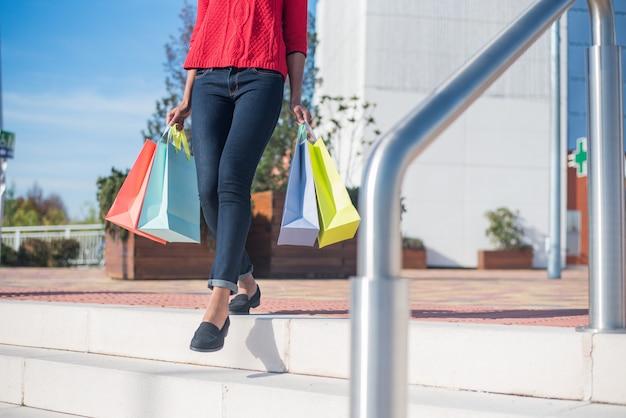 Mujer saliendo de un centro comercial con coloridos bolsos de compras