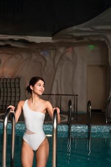 Mujer saliendo de la piscina en el spa