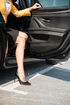 Mujer saliendo de su auto con zapatos de tacones