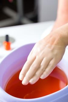 Mujer en salón de uñas con baño de parafina