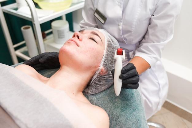 Mujer en salón de belleza durante el procedimiento de mesoterapia con mesoscooter