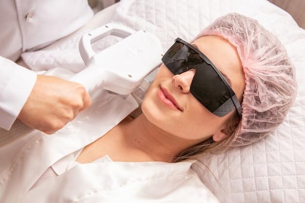 Mujer en salón de belleza profesional durante el procedimiento de fotodepilación