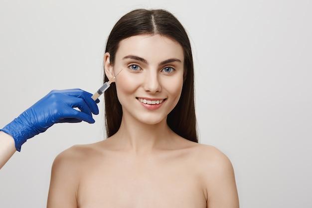 Mujer en salón de belleza sonriendo alegre, recibir inyección bottox cara con jeringa