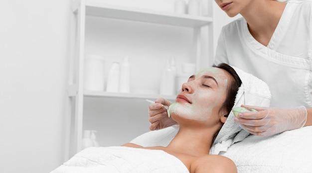 Mujer en salón de belleza para tratamiento facial