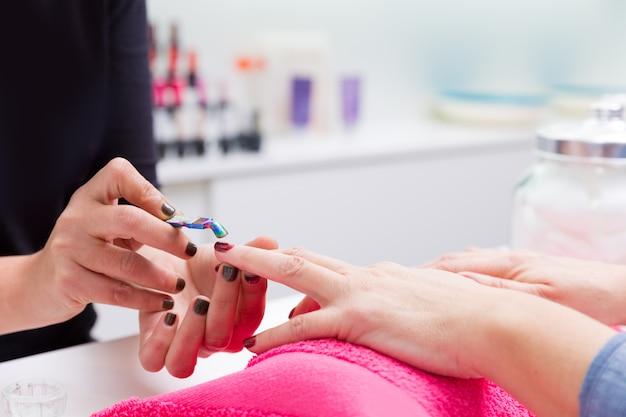 Mujer de salón de uñas con manicura de mano, raspador de cutícula empujador