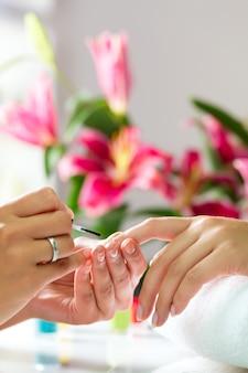 Mujer en salón de manicura recibiendo manicura