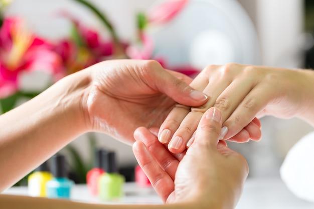 Mujer en salón de manicura recibiendo masaje de manos