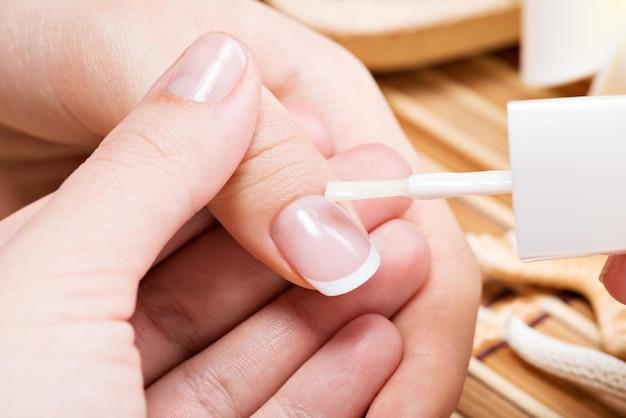 Mujer en un salón de uñas recibiendo manicura. esteticista aplicando esmalte de uñas en una miniatura.