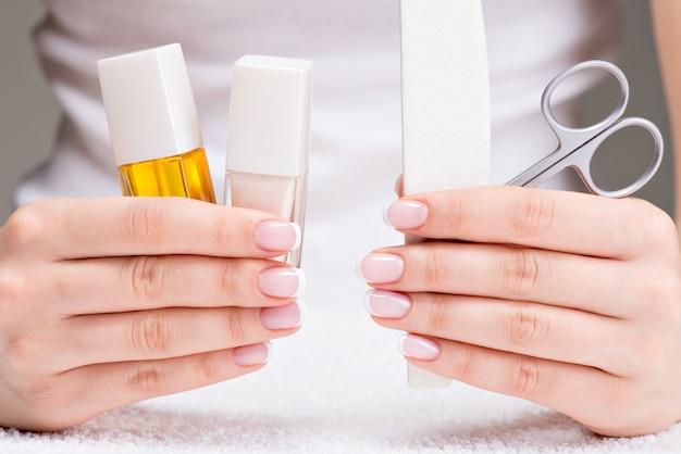 Mujer en un salón de uñas recibiendo manicura por una esteticista. concepto de tratamiento de belleza.