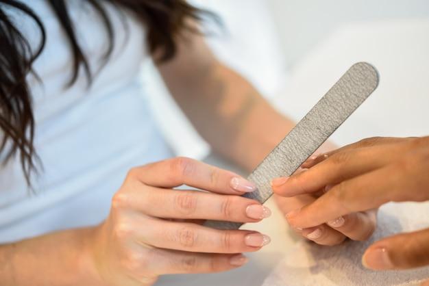 Mujer en un salón de uñas recibiendo una manicura con una lima de uñas