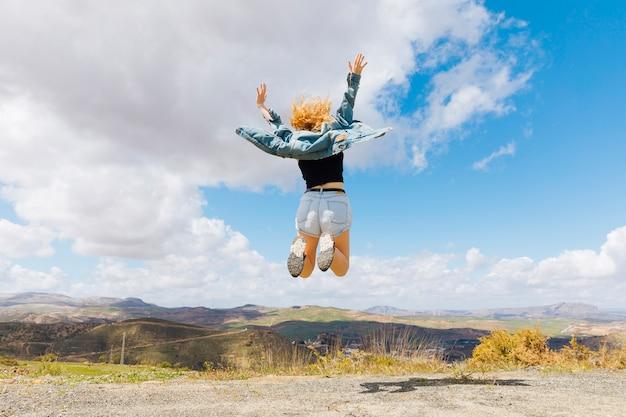 Mujer saltando de alegría en la cima de una colina