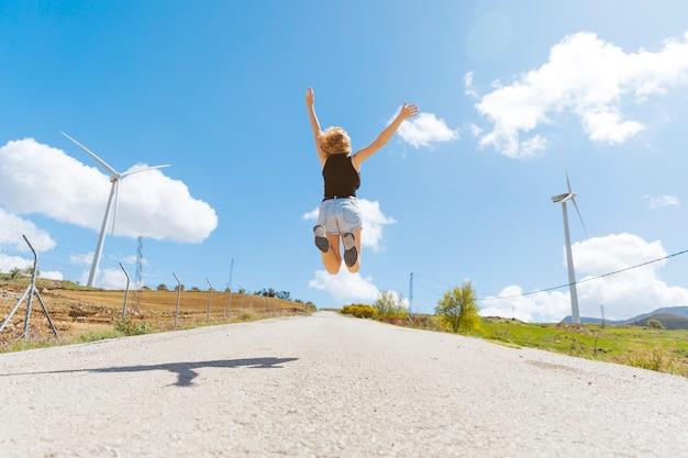 Mujer saltando en carretera vacía