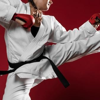 Mujer saltando con guantes de box sobre fondo rojo.