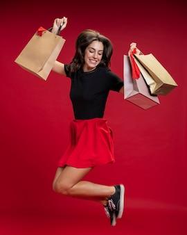 Mujer saltando mientras sostiene sus bolsas de compras