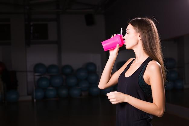 Mujer saludable fitness con deporte batido de proteínas en el gimnasio