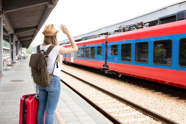 Mujer saludando al tren desde atrás