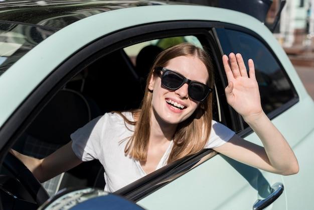 Mujer saludando desde el coche antes del viaje