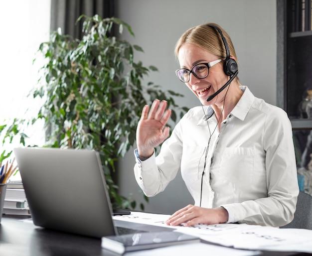 Mujer saludando a sus alumnos en línea