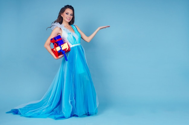 Mujer de san valentín en vestido con caja con regalos sobre un fondo azul en el estudio.regalo de niña agradable sorprendido y asombrado dedo señalando copia espacio.concepto de año nuevo de navidad y día de la mujer.