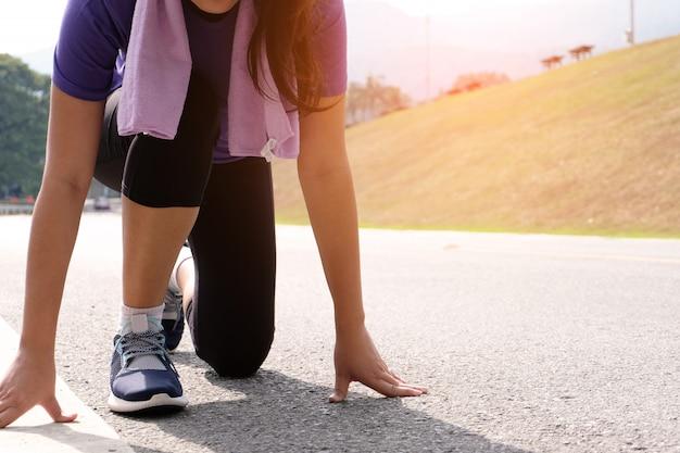 Mujer sana activa que ata las zapatillas deportivas, la asistencia sanitaria del corredor que activa y el concepto de bienestar.