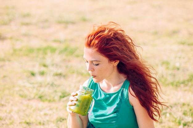 Mujer sana bebiendo jugo de vitaminas verdes en el verano