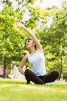 Mujer sana estirando la mano en el parque