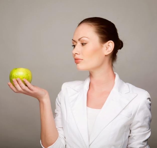 Mujer sana feliz que sostiene la manzana